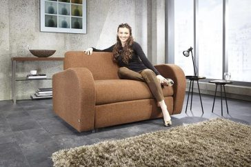 JAYBE CHAIR BED Retro Chair – Sofa from Angle with Model at Just British Sofas